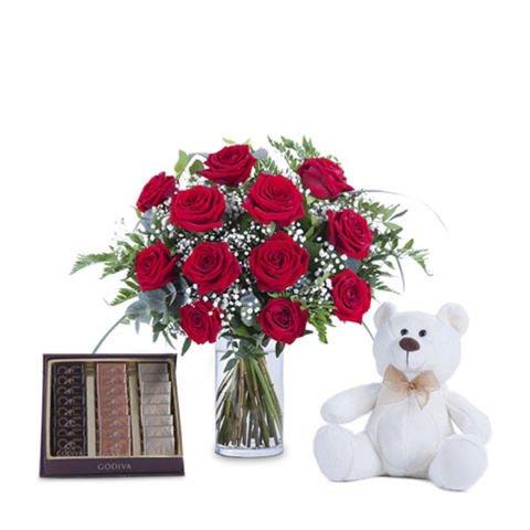 Zärtlicher Korb mit Rosen, Pralinen und einem Teddy
